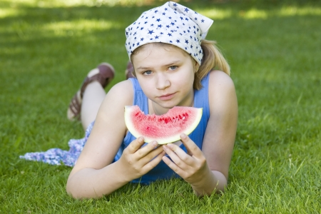 cute little girl eating watermelon on the grass Stock Photo - 13881324
