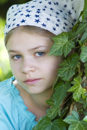 Portrait of young girl standing near tree at summer green park photo