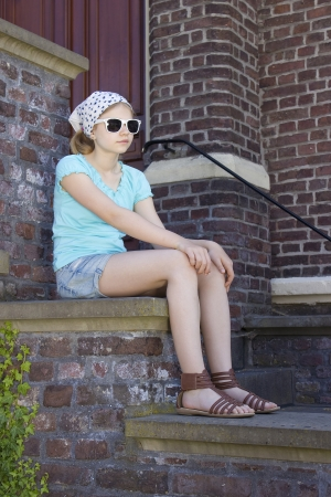little girl sitting on the stairs photo