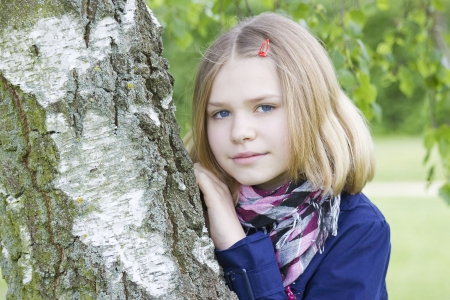 Portrait of young girl standing near birch tree at summer green park photo