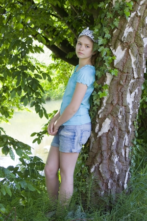 young girl standing near birch tree in summer green park photo