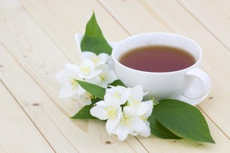 Cup of jasmine tea and jasmine flowers