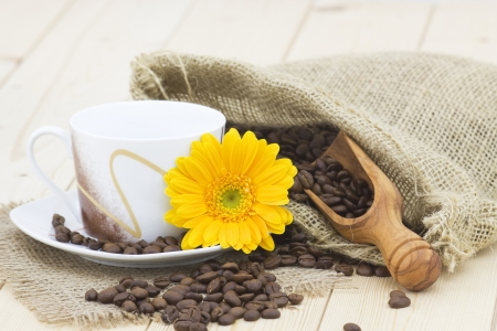 cup of coffee with orange gerbera and coffee beans photo
