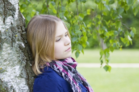 Portrait of young girl standing near birch tree in summer green park photo