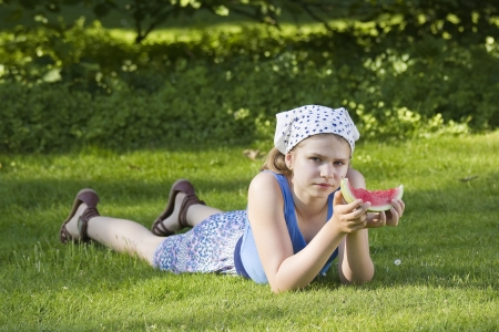 cute little girl eating watermelon on the grass photo