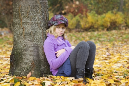 Full length portrait of a little girl sitting under tree in autumn park  photo