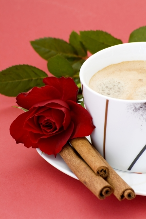 cup of coffee, red rose and cinnamon photo