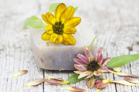 bar of natural soap and flowers photo