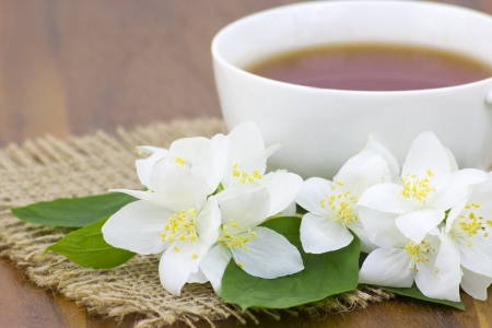 Cup of jasmine tea and jasmine flowers