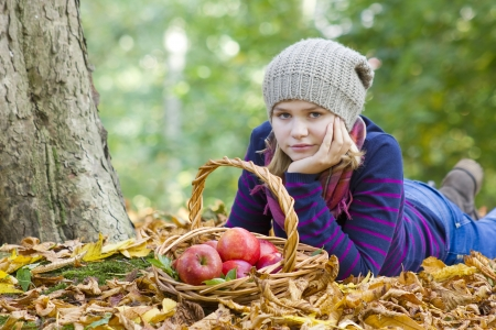 young girl with basket of apples in autumn garden Stock Photo - 16334380