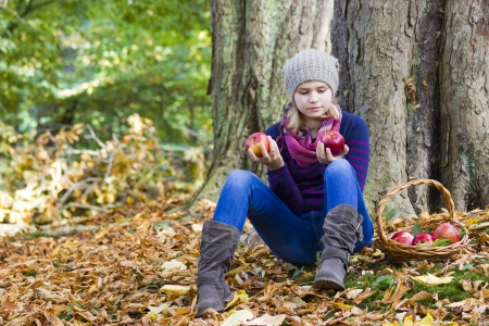 young girl with basket of apples in autumn garden photo