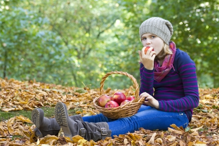 young girl eating red apple in autumn garden photo