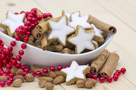 typical christmas cinnamon star cookies, nuts and cinnamon sticks photo
