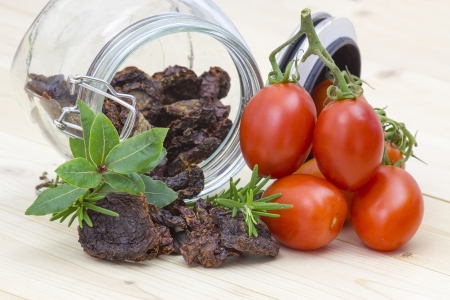 dried tomatoes in a jar and fresh tomatoes photo