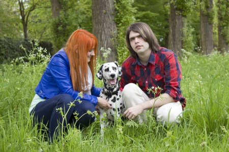 Young couple with a dog on the grass in the park  photo