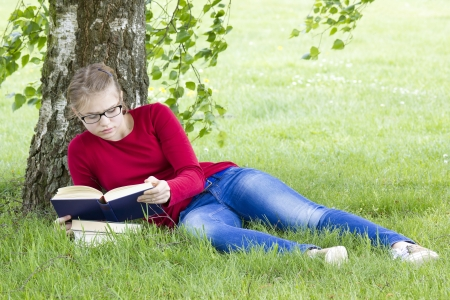 Young girl reading book in park in spring day Stock Photo - 19564546
