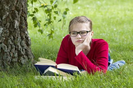 Young girl reading book in park in spring day photo