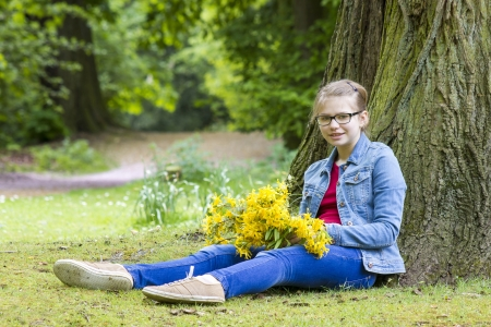 Smiling girl with big bouquet of spring flowers sitting in the park photo