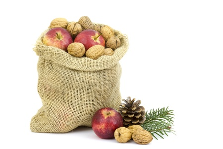Burlap sack full of whole walnuts and apples photo