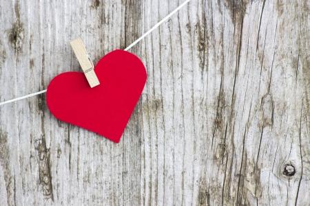 Coeur rouge accroché sur la ligne contre le vieux mur de grain de bois Banque d'images - 23010547