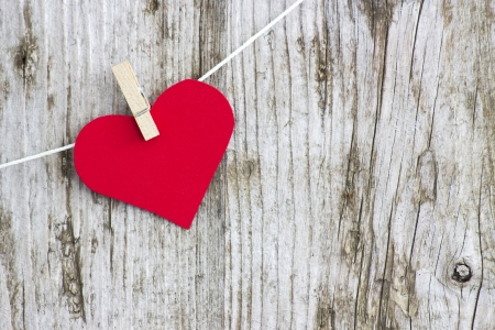 red heart hanging on line against old wood-grain wall Standard-Bild