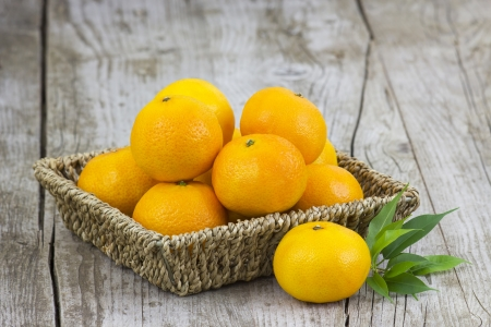 fresh tangerines in a basket on old wooden background photo