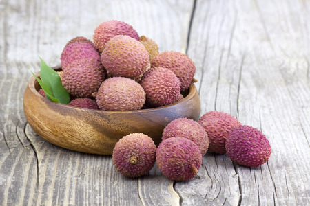 litschi: fresh lychees in a bowl  on wooden table