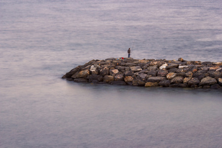 Fisher man with fishing rod on the stone groyne at sunset photo