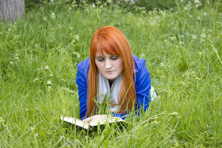 Young woman with red hair reading a book  photo