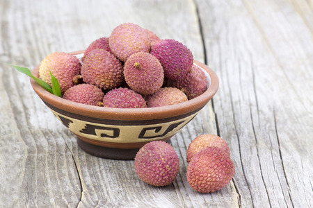 litschi: fresh lychees in a bowl  on wooden background