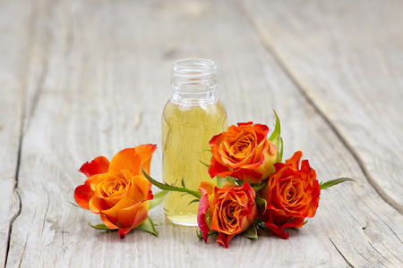 rosas naranjas: ba�o de aceite y naranja rosas sobre fondo de madera vieja Foto de archivo