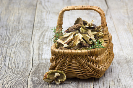 fungous: dried mushrooms in a basket on wooden background