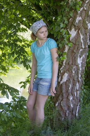european white birch: young girl standing near birch tree in summer green park