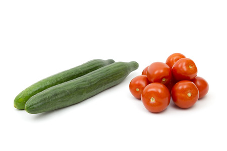 fresh vegetables - tomatoes and cucumbers on white background photo