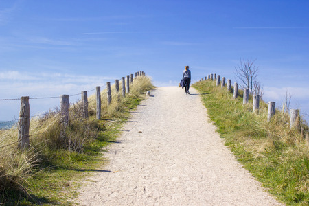 dutch girl: Walking with the dog in the dunes, Zoutelande, Netherlands Stock Photo