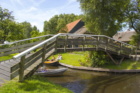 """GIETHOORN, NETHERLANDS - AUGUST 05, 2015: Unknown visitors in the sightseeing boating trip in a canal in Giethoorn. The beautiful city is know as """"Venice of the North""""."""