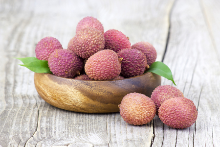 lechee: fresh lychees in a bowl  on wooden background