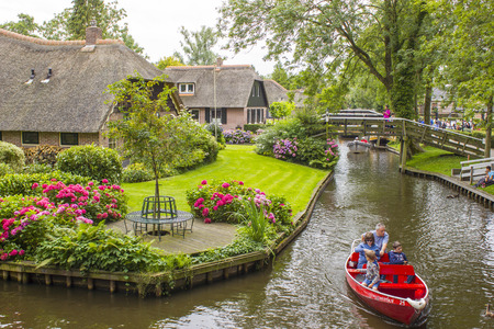 GIETHOORN, NETHERLANDS - AUGUST 01 2017: Unknown visitors in the sightseeing boating trip in a canal in Giethoorn. The beautiful houses and gardening city is know as
