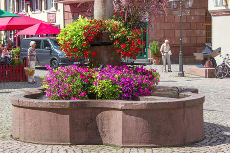 HASLACH, GERMANY - JULY 26 2017 Fountain with flowers in Haslach, Black Forest, Baden-Wurttemberg, Germany, Europe