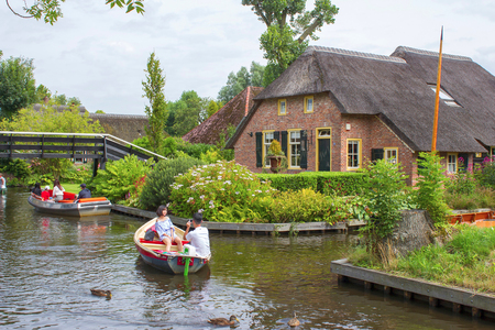 GIETHOORN, NETHERLANDS - AUGUST 01 2017: Unknown visitors in the sightseeing boating trip in a canal in Giethoorn. The beautiful houses and gardening city is know as Venice of the North. Editorial