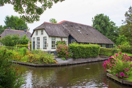 GIETHOORN, NETHERLANDS -typical dutch county side of houses and gardens