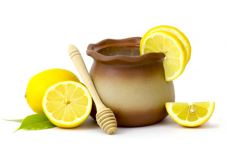 clay pot with honey and fresh lemons on white background Stock Photo