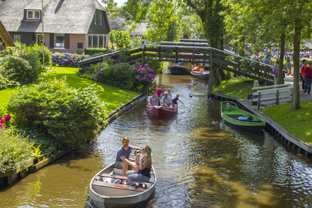 GIETHOORN, NETHERLANDS - AUGUST 05 2013: Unknown visitors in the sightseeing boating trip in a canal in Giethoorn. The beautiful houses and gardening city is know as Venice of the North.