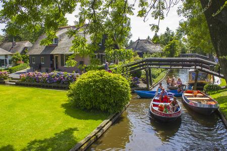 """GIETHOORN, NEDERLAND - AUGUSTUS 05 2013: Onbekende bezoekers in de sightseeingboottocht in een kanaal in Giethoorn. De prachtige huizen- en tuinstad staat bekend als """"Venetië van het noorden"""". Redactioneel"""