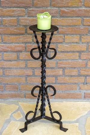 Retro candlestick with candle, on brick wall