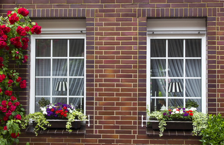 brick wall with windows and flower boxes with flowering plants, Geldern, Germany