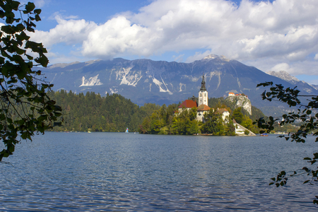 Catholic church situated on an island on Bled lake with mountains on the background