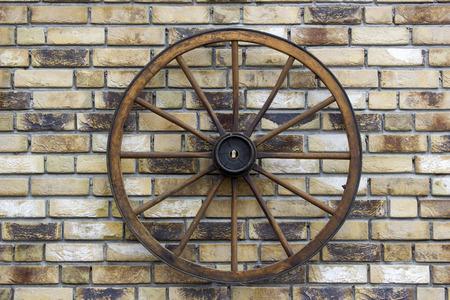 Rural wagon wheel on a brick wall Stock Photo