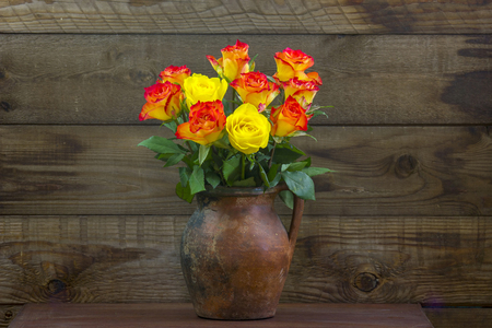 orange and yellow roses in a vase on wooden background