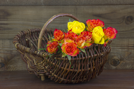 orange and yellow roses in a basket on wooden background